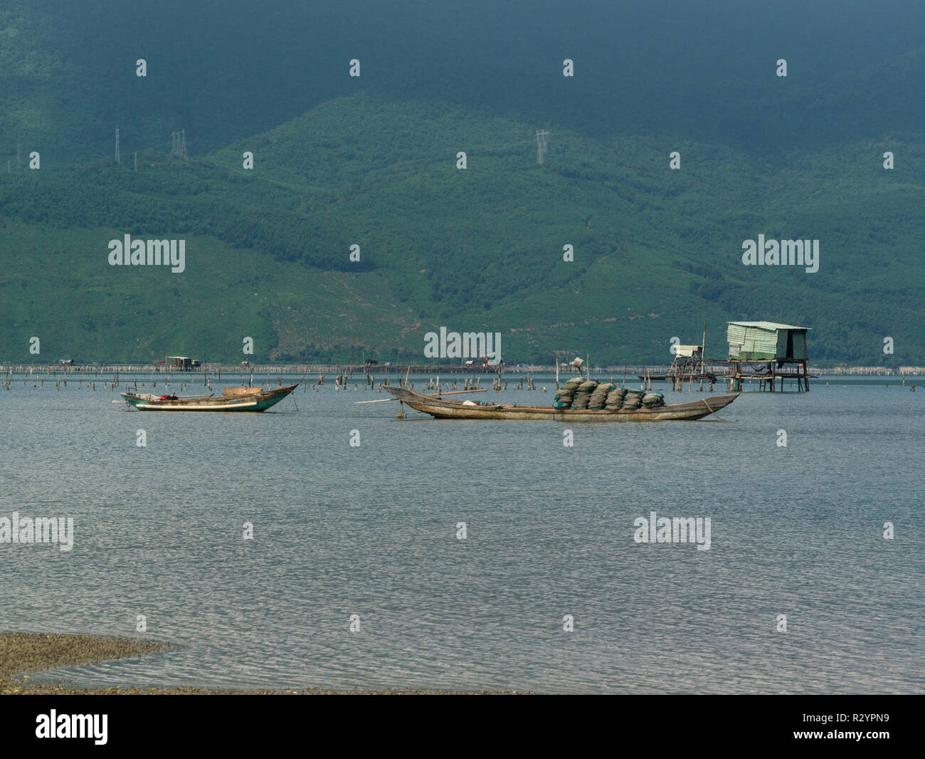 Fishing boats and shed  moored in Lang Co village lagoon South Vietnam between Lap An Lagoon and South China Sea known for seafood - Stock Image