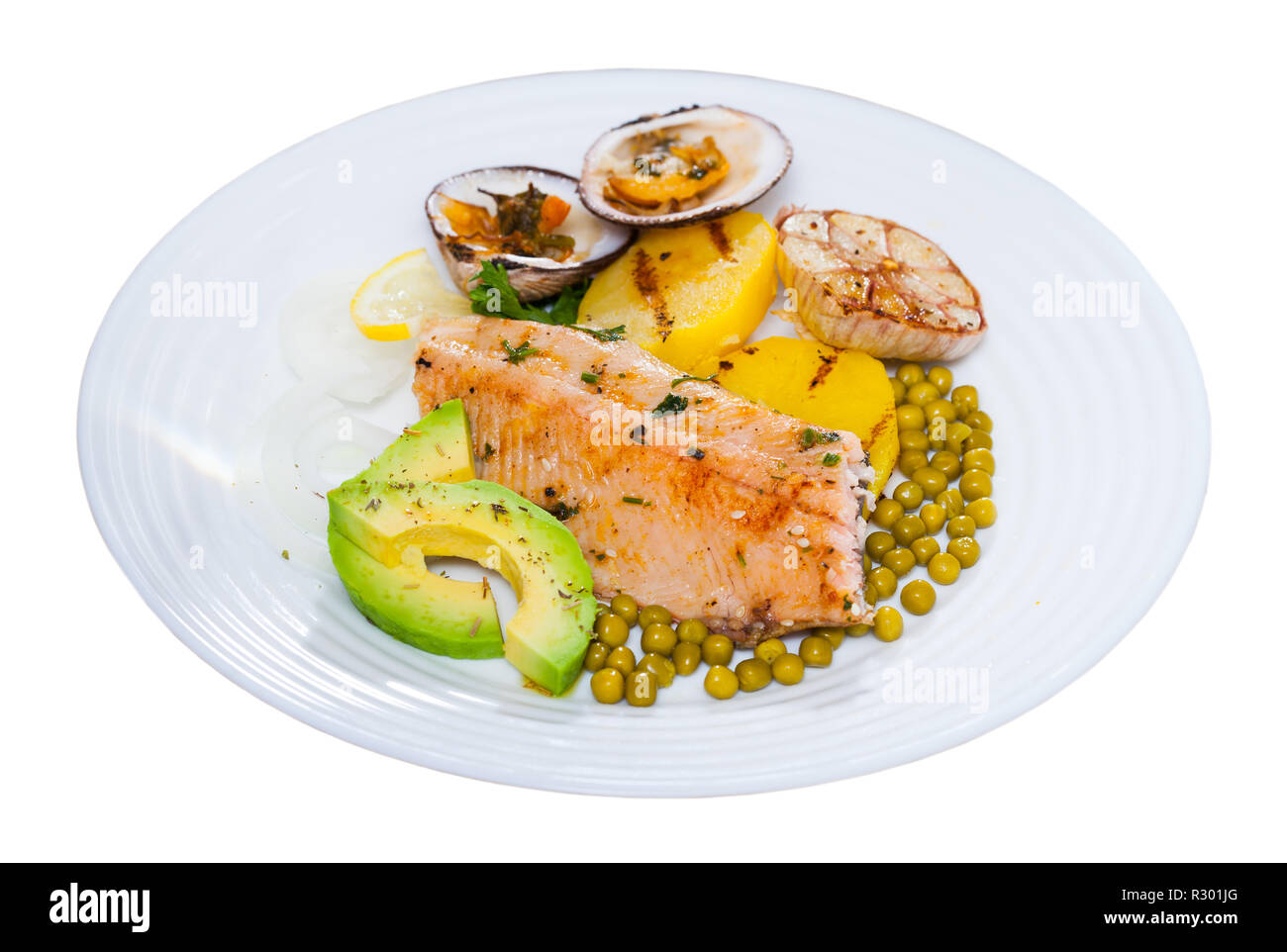 Fried trout fillet served with vegetables and almendra de mar. Isolated over white background - Stock Image