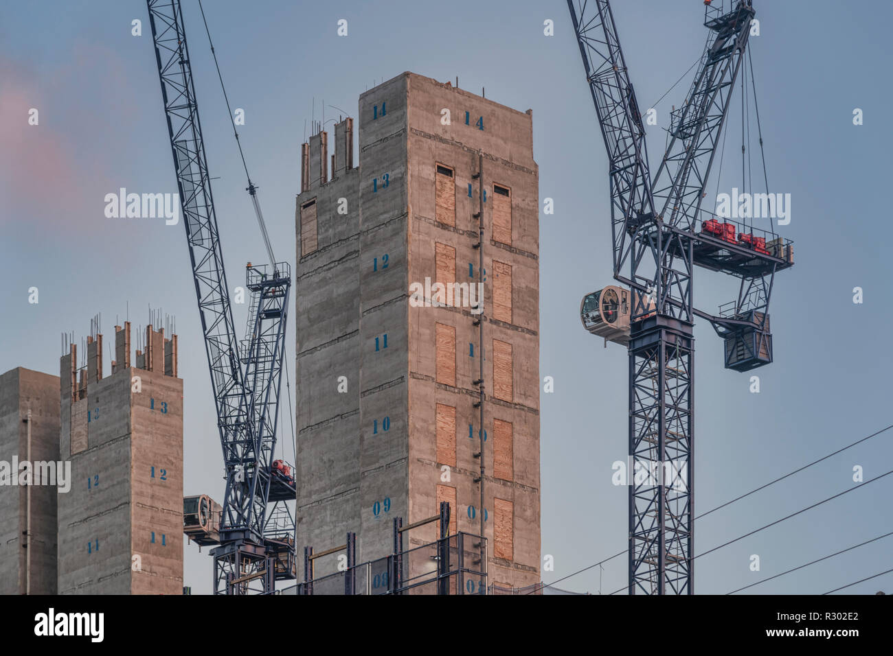 Construction site with concrete core and two tower cranes - Stock Image