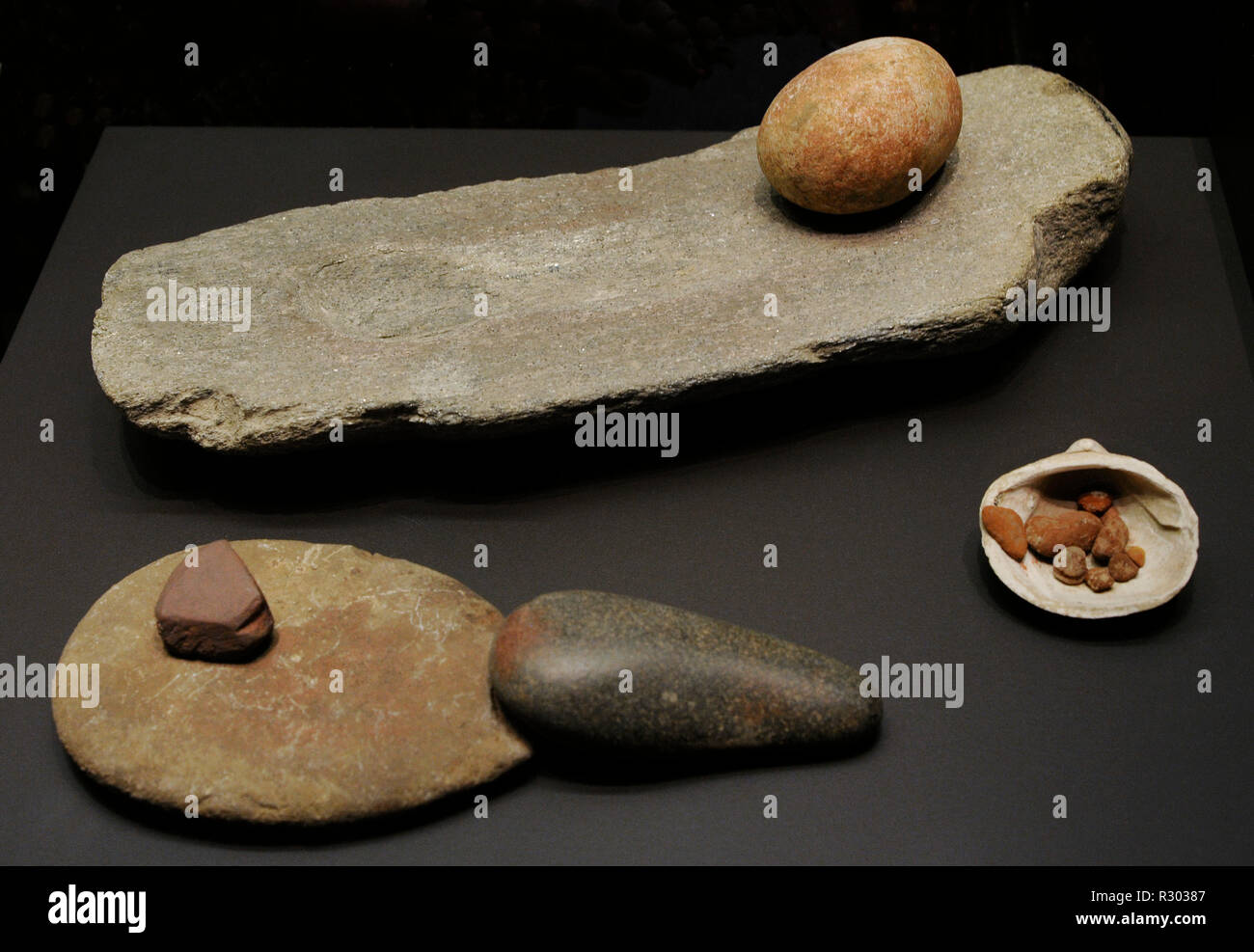 From left to right and from back to front: Grindstone. El Garcel (Antas, Almeria province, Andalusia) and El Higueron Cave (Rincon de la Victoria, Malaga province, Andalusia); Grindstone, pestle and dye. El Higueron Cave (Rincon de la Victoria, Malaga province, Andalusia) and Ochre pot with traces of dye. La Encantada (Almanzora Caves, Almeria province, Andalusia). National Archaeological Museum. Madrid. Spain. - Stock Image