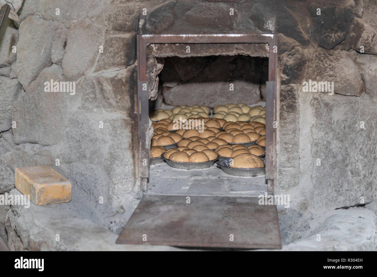 Kealakekua, Hawaii - Members of the Kona Historical Society, helped by tourists, bake bread in a Portuguese stone oven. The oven is a reproduction of  - Stock Image