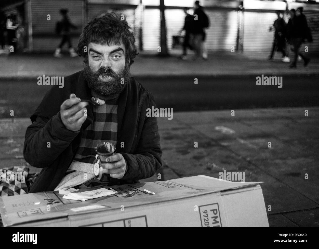 homeless man sitting on London street eating of a cardboard box - Stock Image