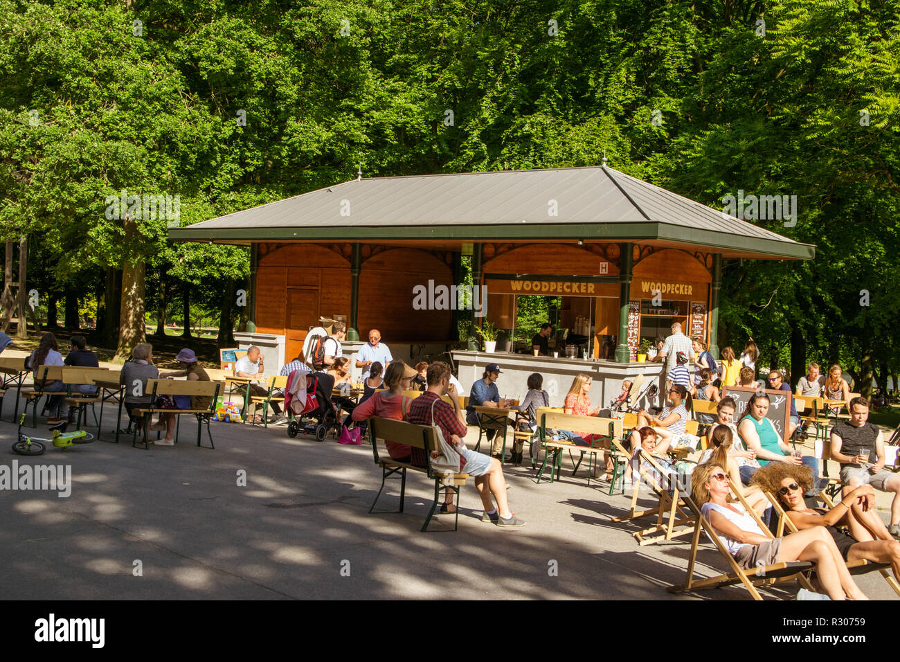 Locals having a cold drink and a rest in the city park Bois de la cambre during a hot summer day in Ixelles, Brussels, belgium - Stock Image