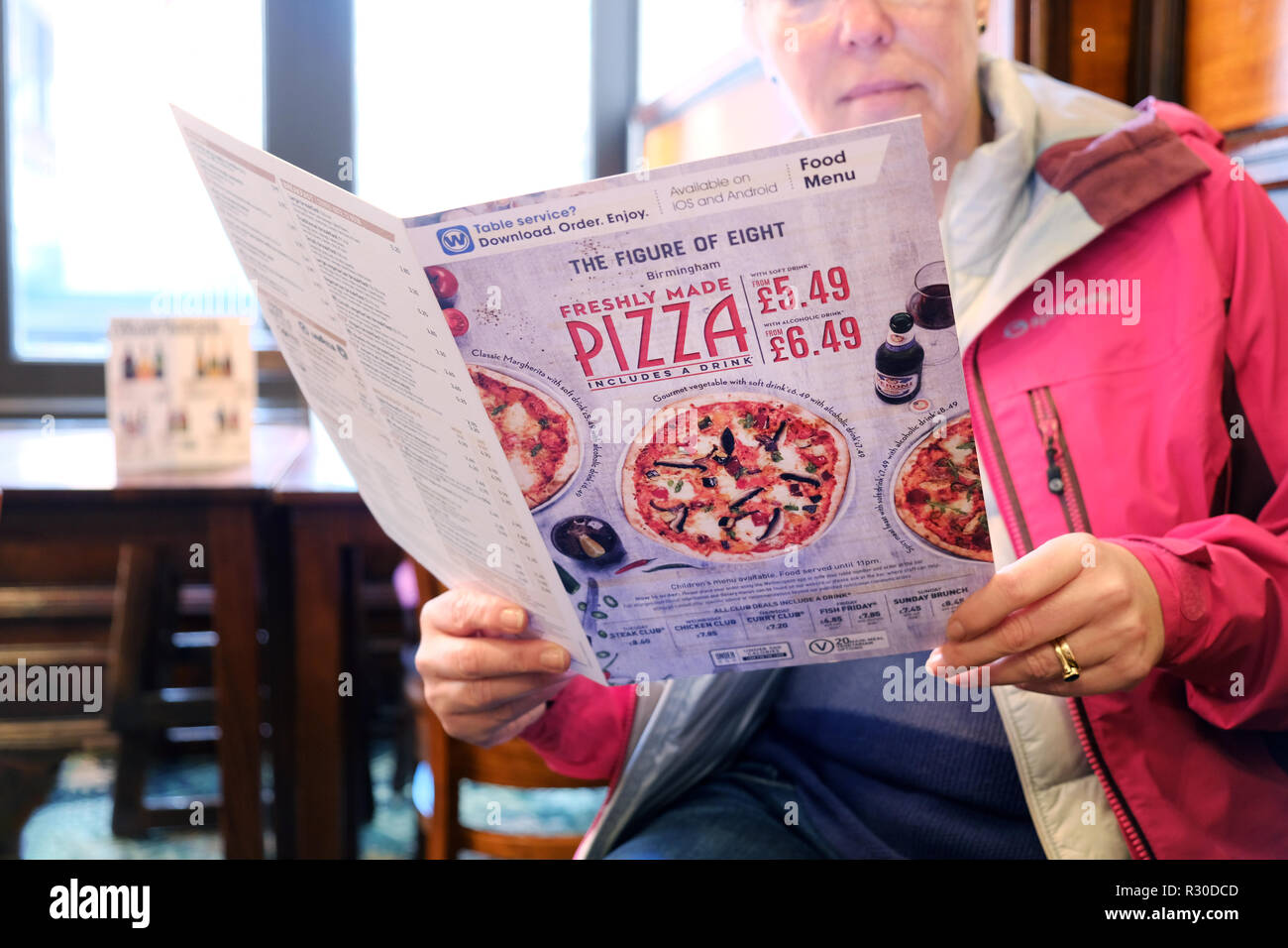 A female customer at a jd wetherspoons pub studies the menu card for food and meal options. The menu card cover features the chains pizza offers - Stock Image