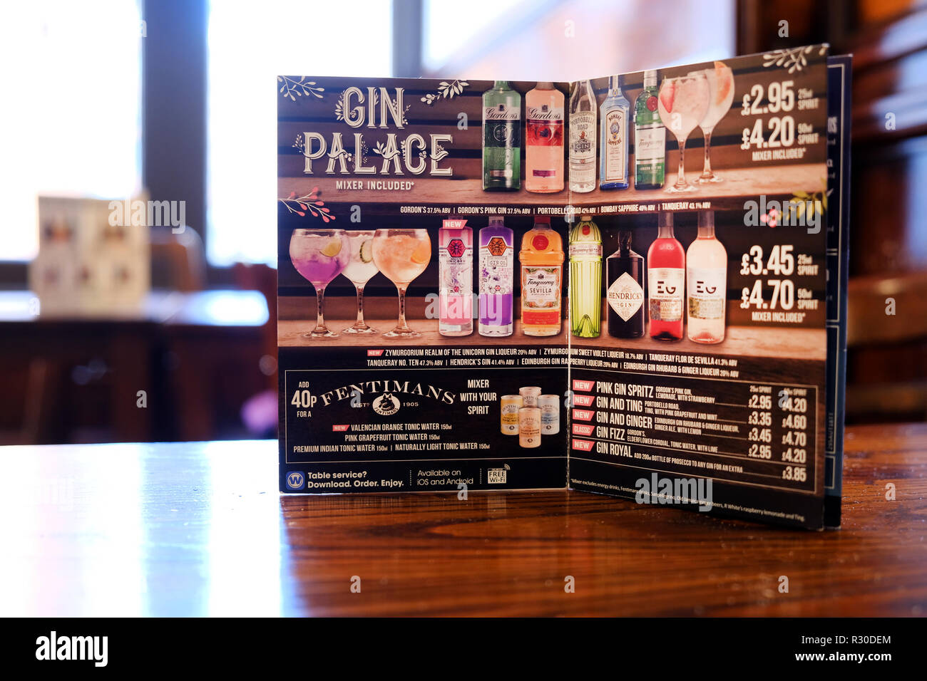 A JD Wetherspoons drinks menu card showing the Gin Palace options for the pubs customers. its propped open on a table inside one of their pubs - Stock Image