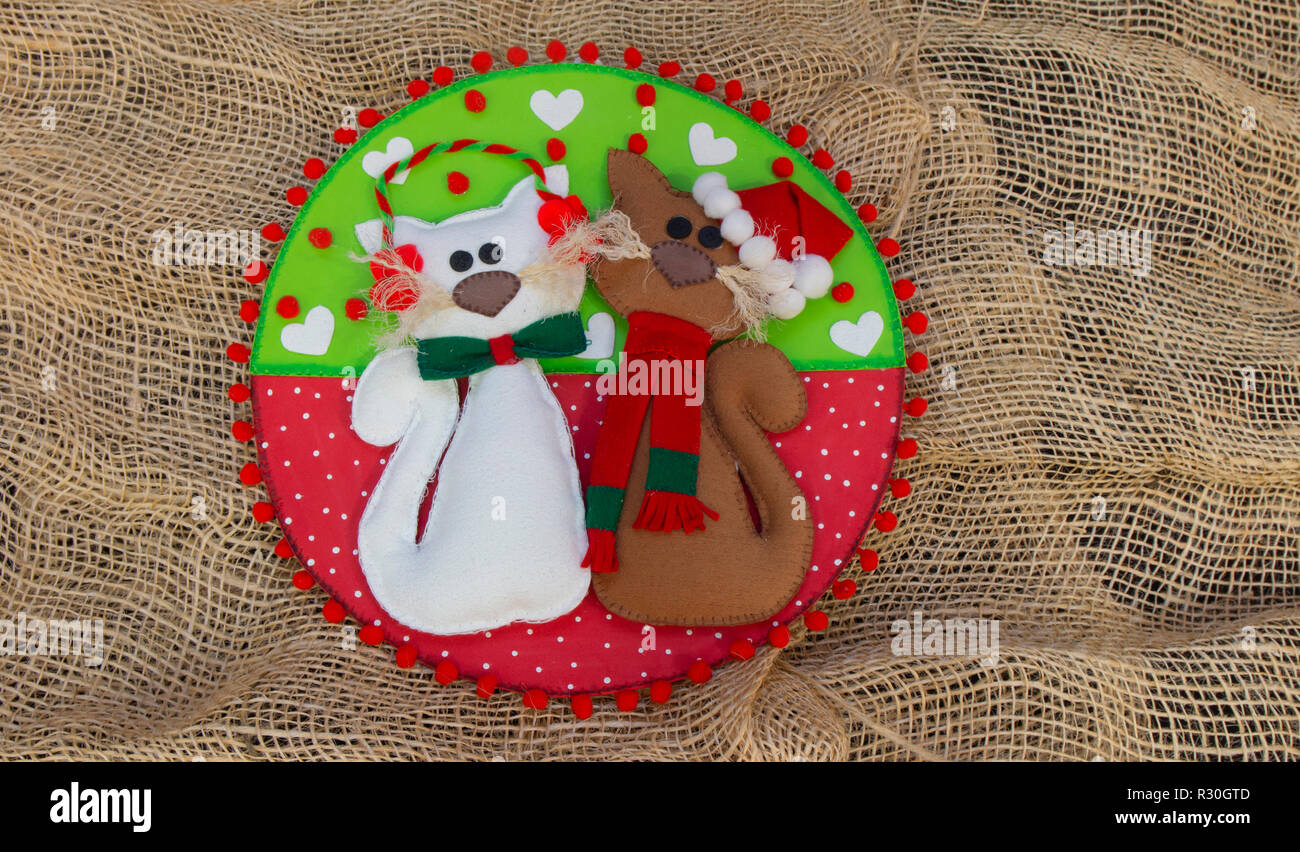 Pair of cats made in foam with Christmas decoration on a circle of red and green with white hearts, on a rustic background of jute fabric - Stock Image