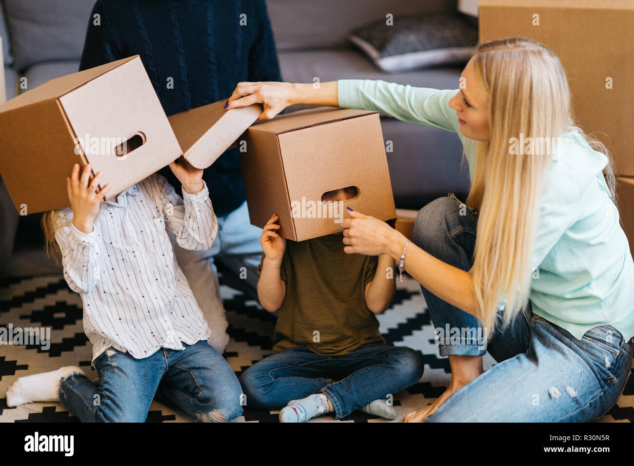 Picture of young married couple with indulging children sitting on floor among cardboard boxes in new apartment - Stock Image
