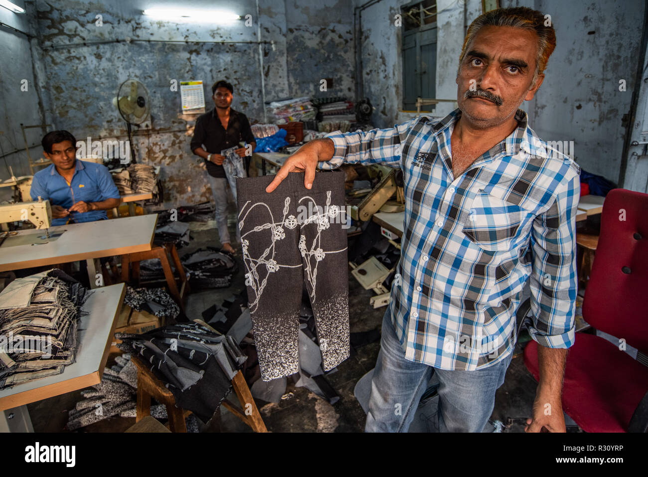 A tailoring shop owner shows off his wares posing in his small sweatshop in Ahmedabad, while his other employees look on. Gujarat, India - Stock Image