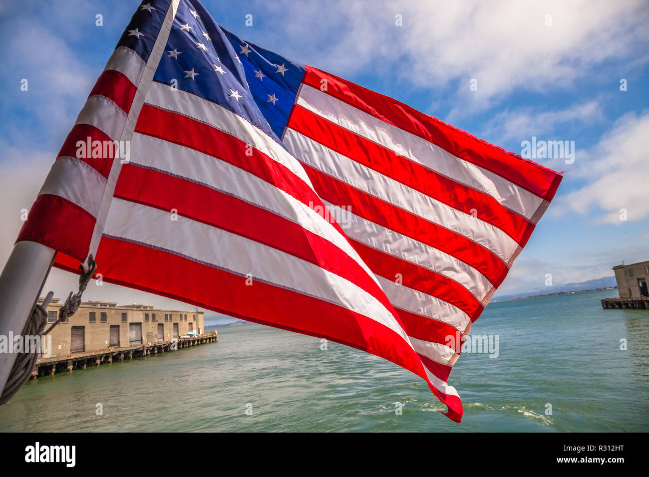 Alcatraz tour to Alcatraz island by boat trip in San Francisco Bay, California, United States. Ferry boat with American flag waving in San Francisco pier. - Stock Image
