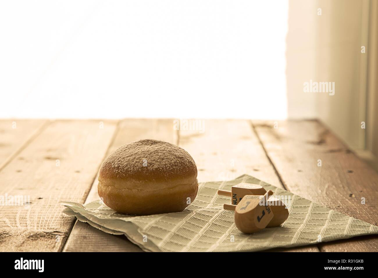 Still life for jewish holiday Hanukkah celebration concept-donut and dreidels on rustic table.Copy space ,Baclight  Shallow DOF - Stock Image
