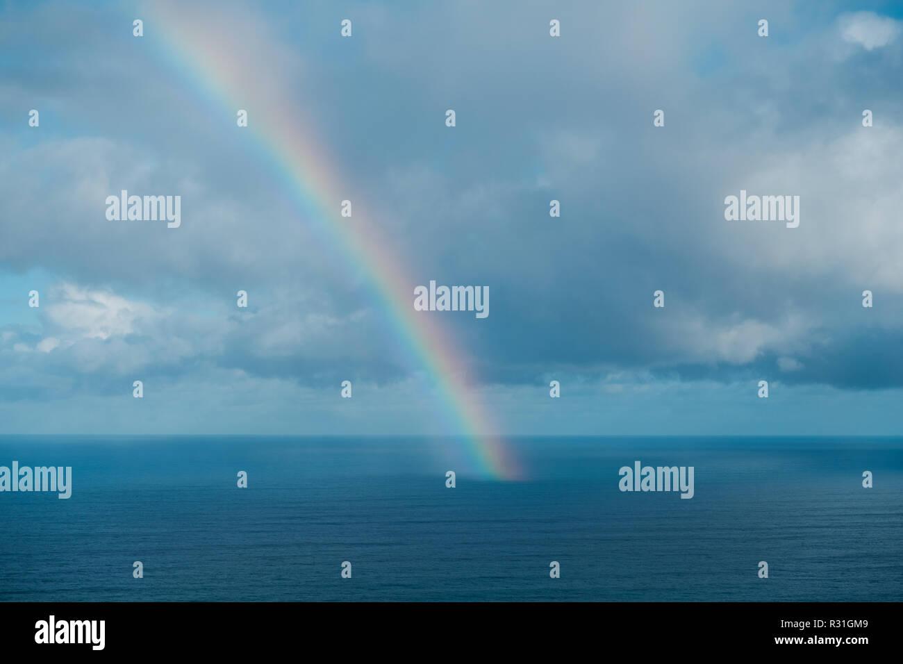 rainbow on ocean, rainbow ending on ocean - Stock Image