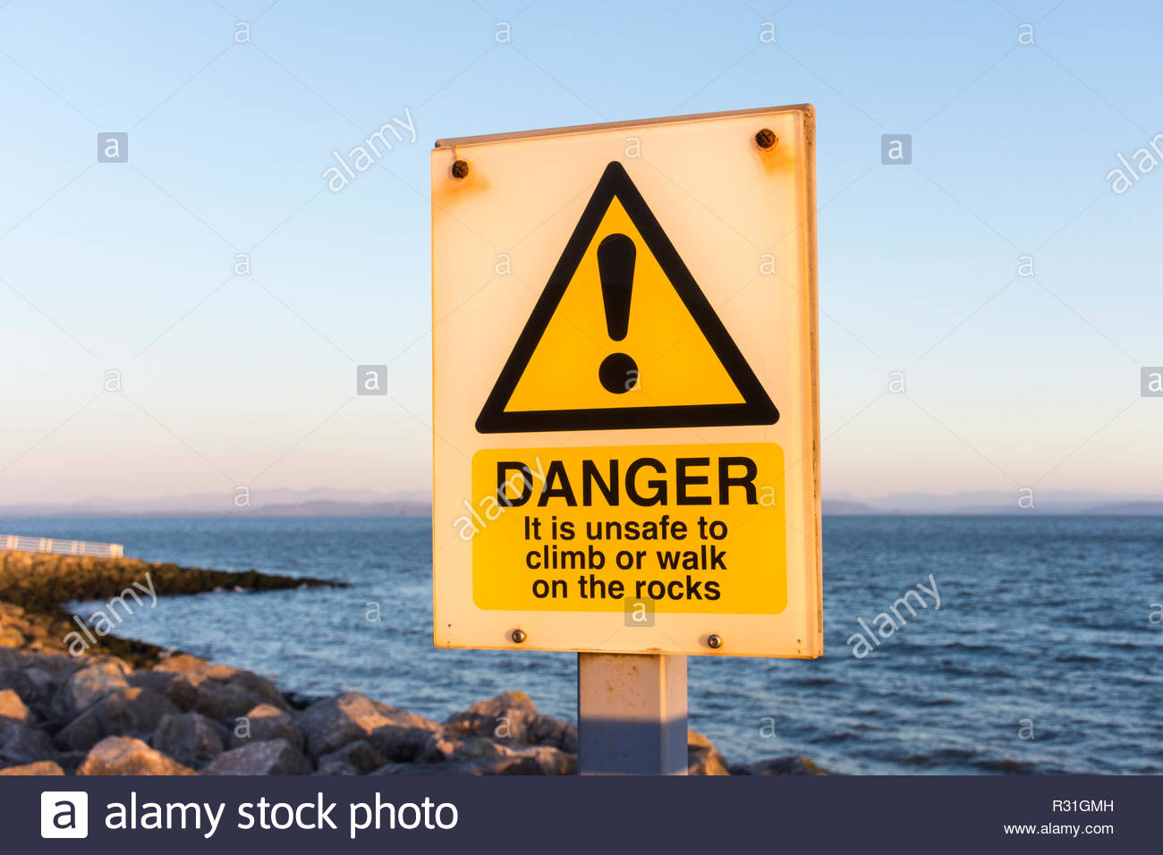 Sign on the promenade at Morecambe - Danger, it is unsafe to climb or walk on the rocks - Stock Image