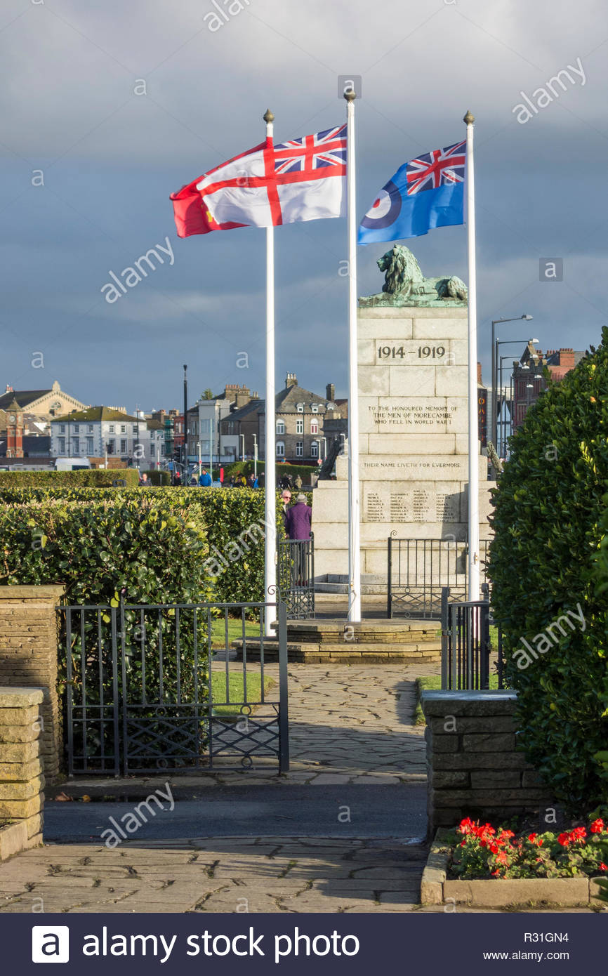 Flags for the Army, Royal Navy and Royal Air Force flying by the war memorial on Marine Road, Morecambe, Lancashire on 11 November 2018 - Stock Image