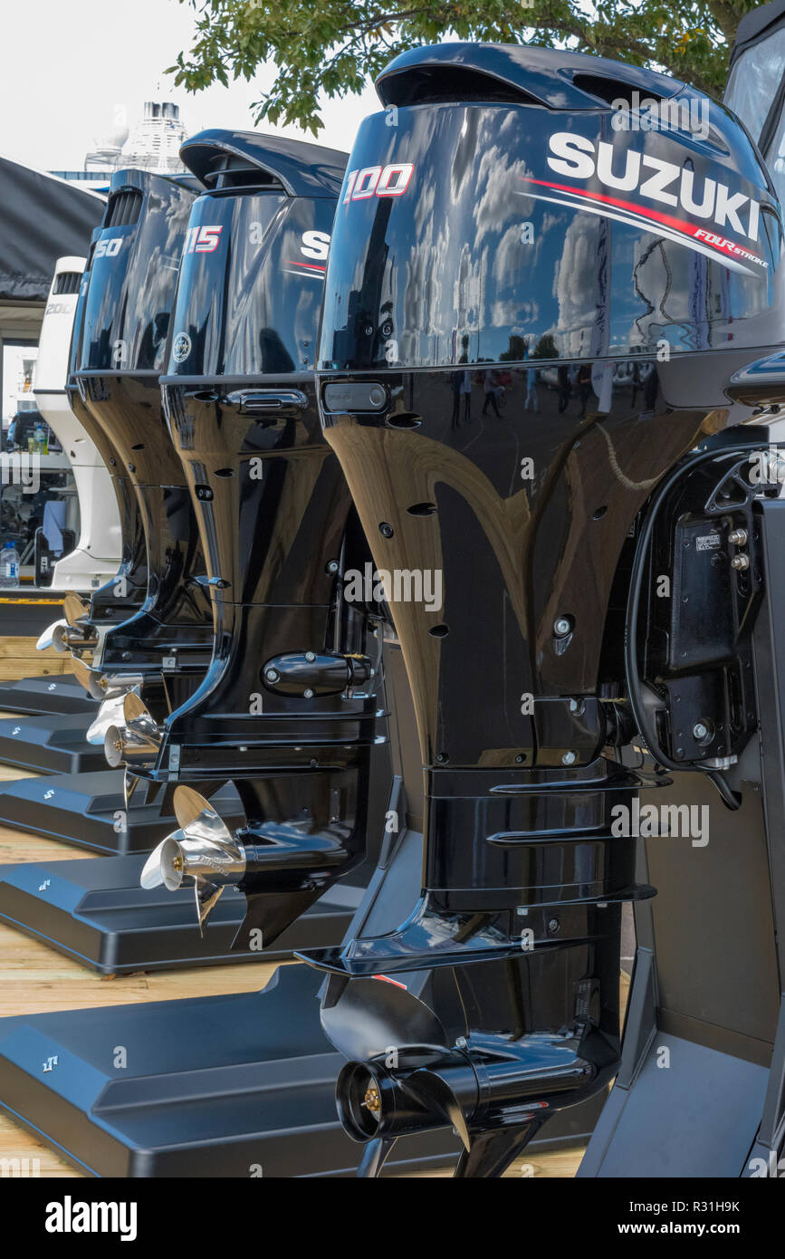 a row of brand new suzuki outboard engines on display at southampton international boat show on a displaying stand. - Stock Image