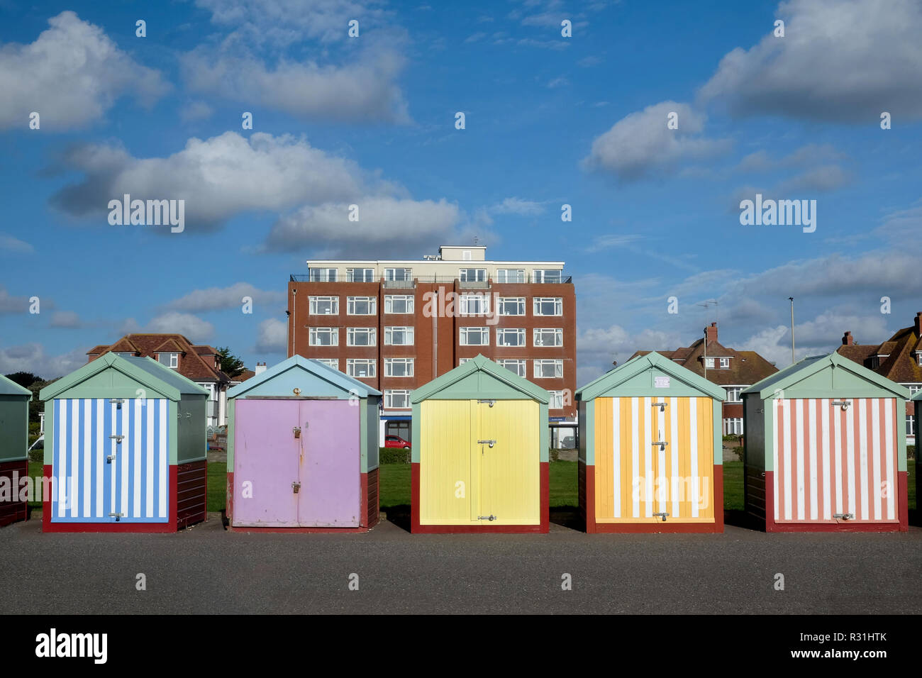 Brighton seafront five beach huts, with multi coloured doors of yellow, pink, black stripes behind is an appartment building and blue sky Stock Photo
