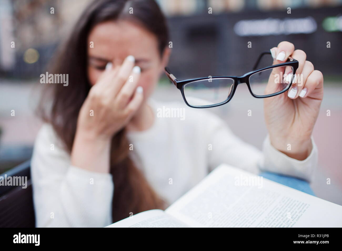 Closeup portrait of attractive female with eyeglasses in hand. Poor young girl has issues with vision. She rubs her nose and eyes out of fatigue. A student tired to study and read books - Stock Image