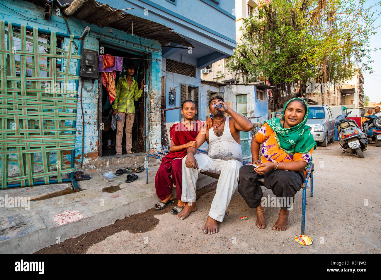 A man with his wife and sister sit in the street for a causal break, while a man stands at the doorway. Ahmedabad, India - Stock Image