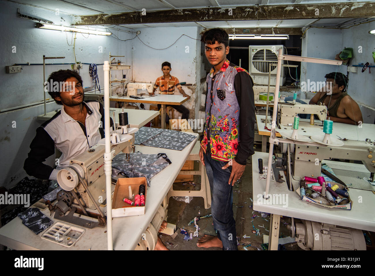 An Ahmedabad tailoring sweatshop with four young tailors, Gujarat, India - Stock Image