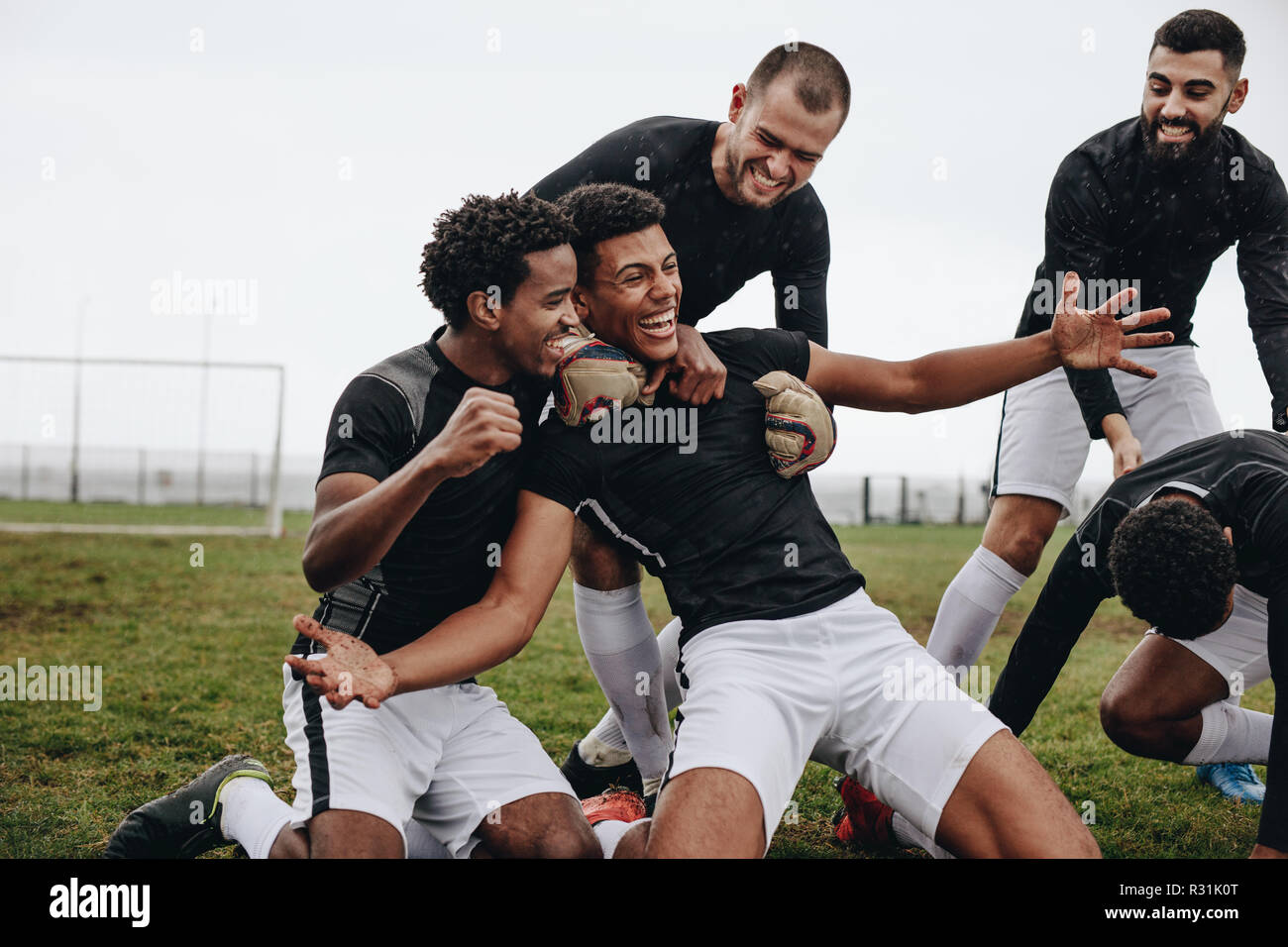 Football players celebrating success on the field. Happy footballer sitting on his knees with open arms after scoring a goal being cheered by his team - Stock Image