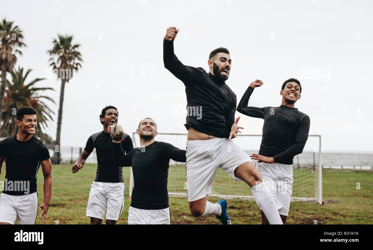 Soccer players jumping in air and pumping their fists celebrating a win. Football players celebrating success on the field. - Stock Image