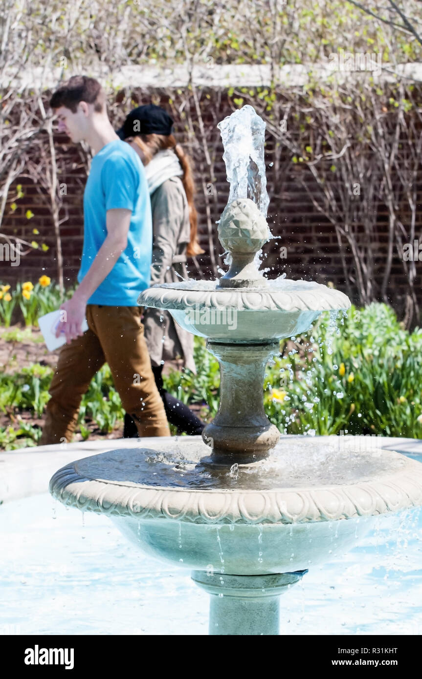 A young couple walking past a decorative water fountain. Stock Photo