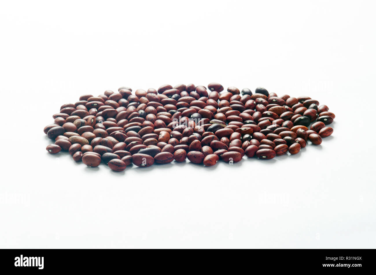 Small dried red beans on white, a good source of fiber and potassium Stock Photo