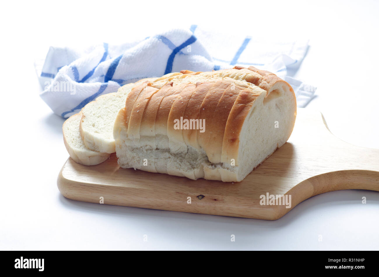 Loaf of sliced italian white bread on wood cutting board - Stock Image