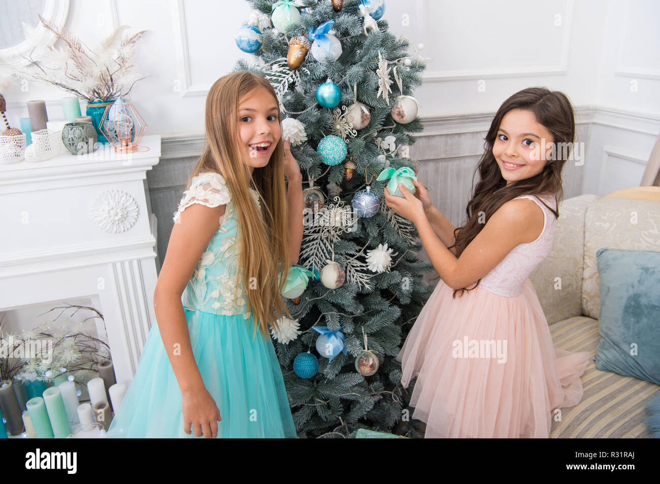 Sisters decorating tree. Cherished holiday activity. Kids fashionable dresses decorating christmas tree. Family tradition concept. Girls decorating christmas tree together. Siblings busy decorating. Stock Photo