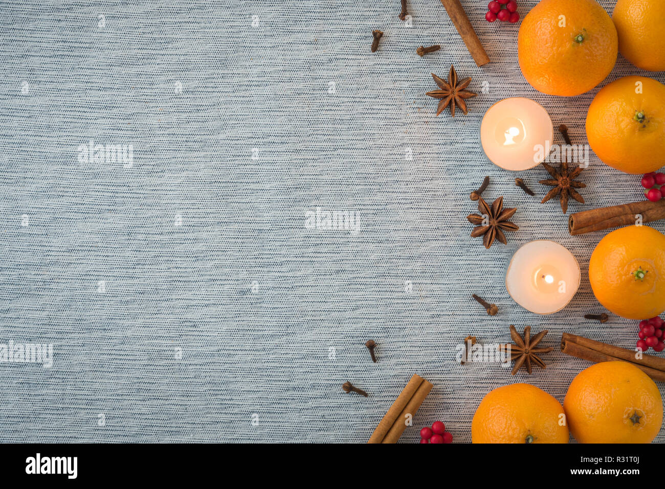 Flat lay seasonal arrangement of oranges, spices, and candles - Stock Image