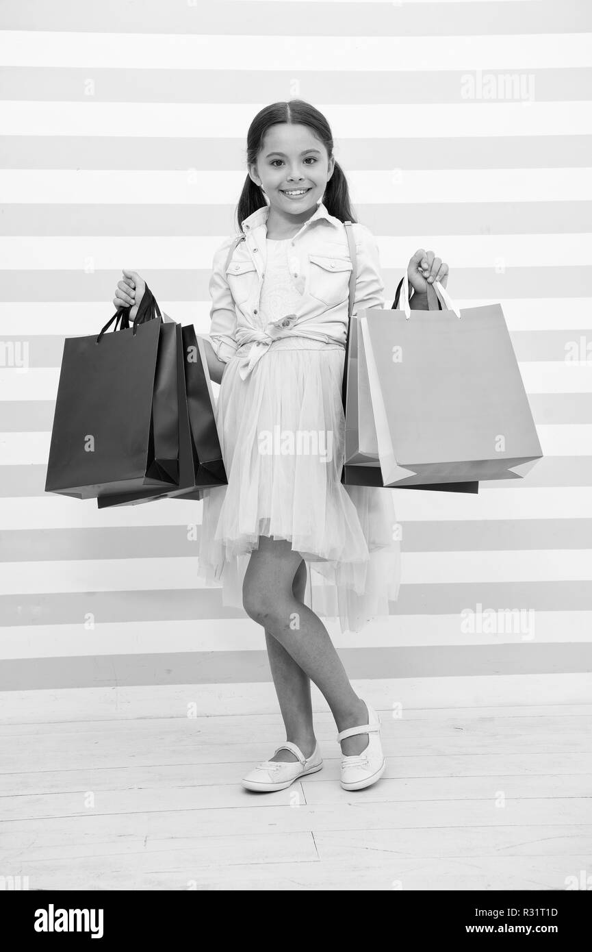 Shopping is her favorite activity. Child girl carries shopping bags striped bacground. In all ages women adore shopping. Kid girl enjoy shopping sale season. Girl smiling satisfied face holds bags. - Stock Image