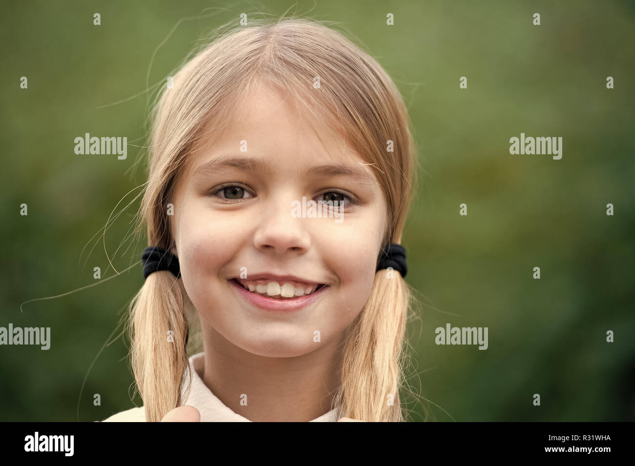 Girl happy smile with blond hair ponytails on natural environment. Child beauty, look, hairstyle concept. - Stock Image