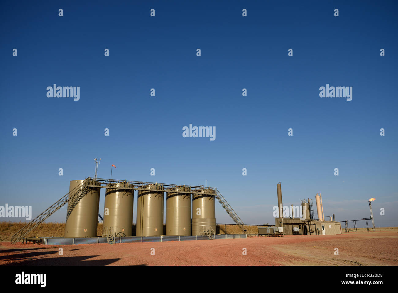 Natural gas flare, crude oil, well site, production holding tanks, blue sky, Niobrara shale, Wyoming, copy space - Stock Image