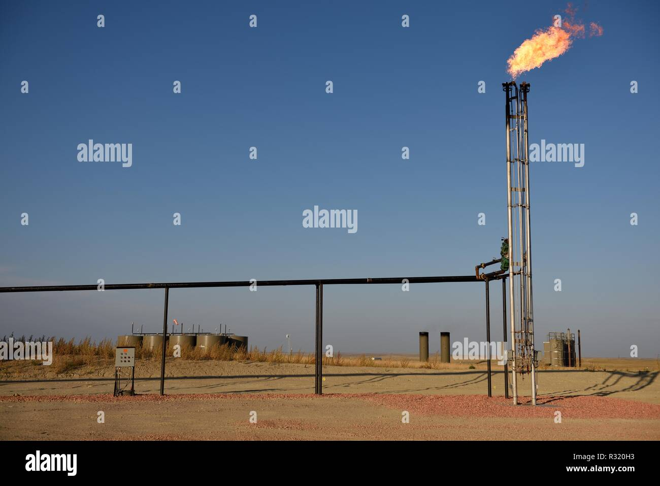 Natural gas flaring, venting, crude oil production drilling site, Wyoming, clear sky, Powder River Basin, Wyoming, copy space - Stock Image