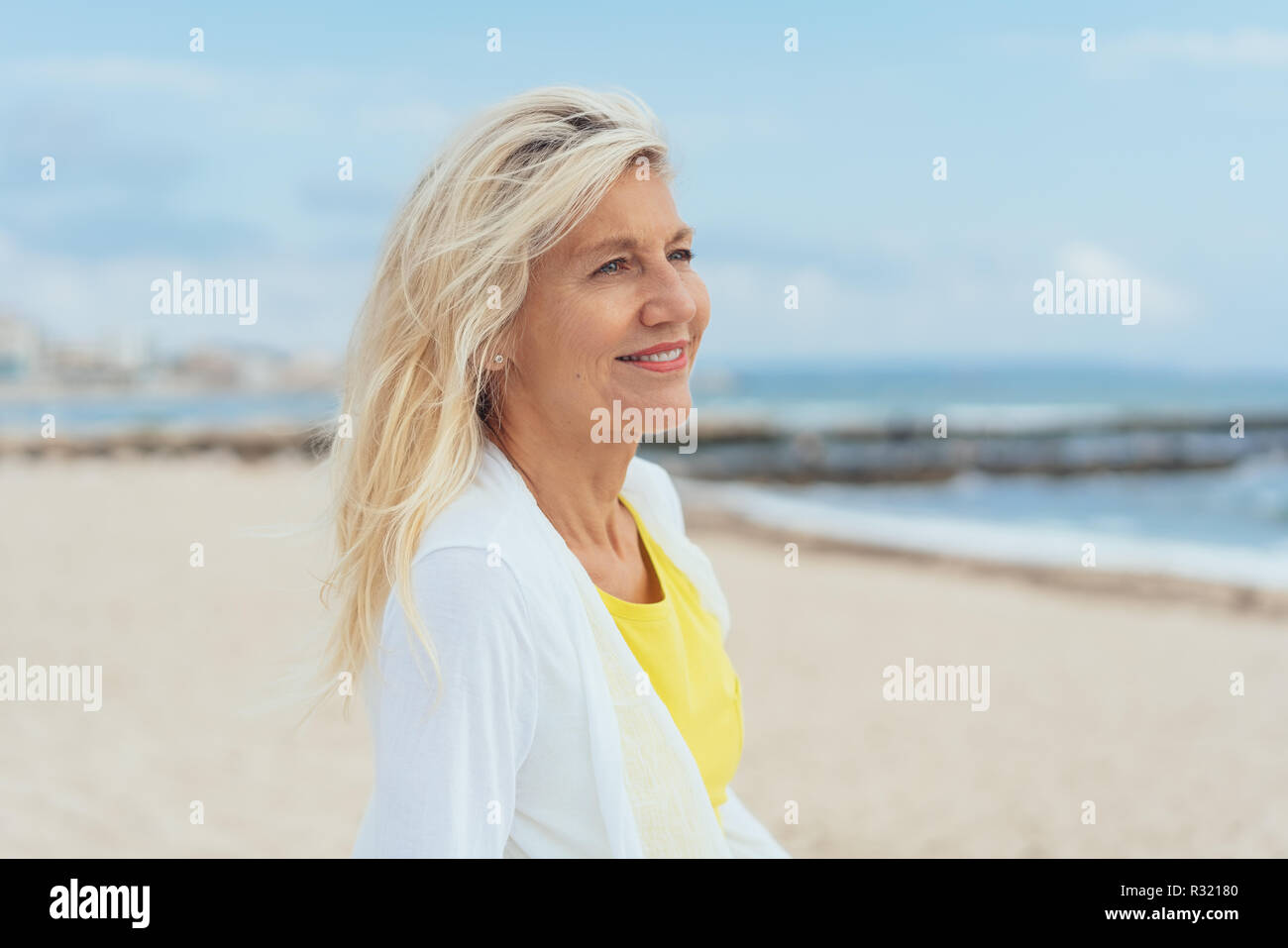 Happy vivacious blond woman with tousled hair standing on a windswept tropical beach looking out over the ocean - Stock Image