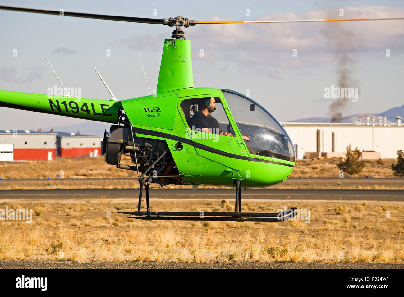 An instructor and student pilot fly a two-seat R22 Beta II helicopter made by the Robinson Helicopter Company, at a small city airport in Bend, Oregon - Stock Image