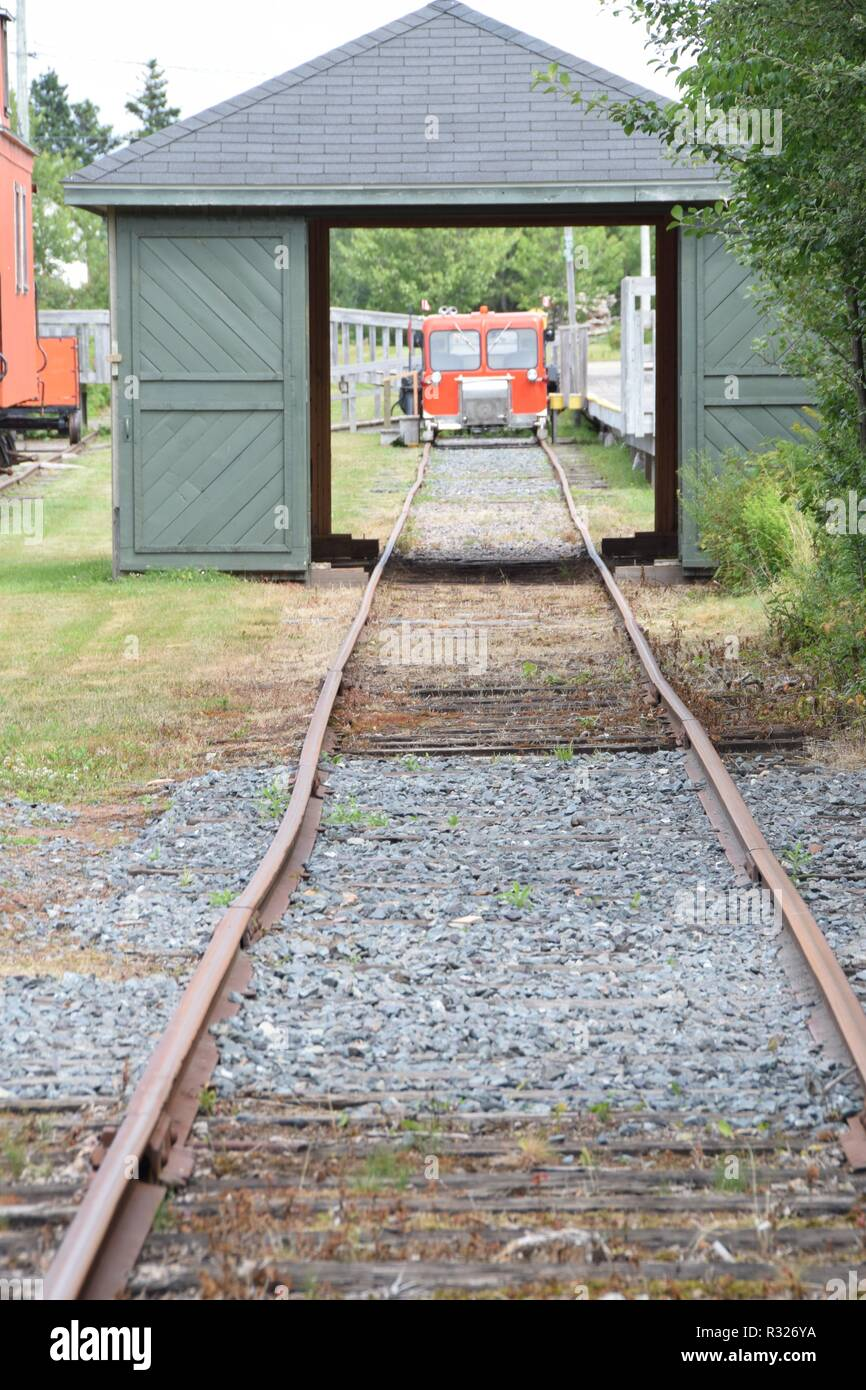 Small Train on tracks through a shed - Stock Image