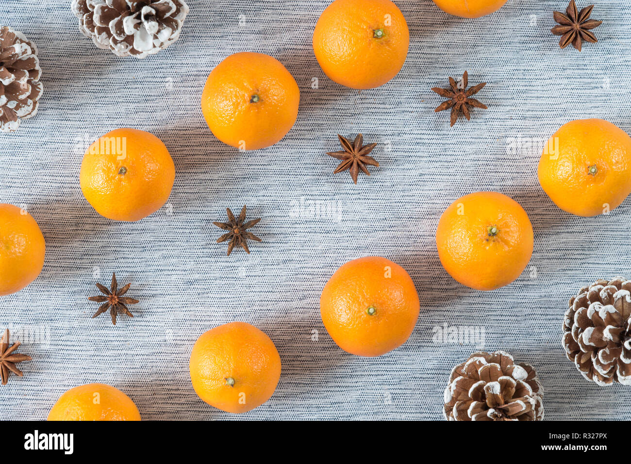 Diagonal rows of oranges, star anise, and pinecones on grey background - Stock Image