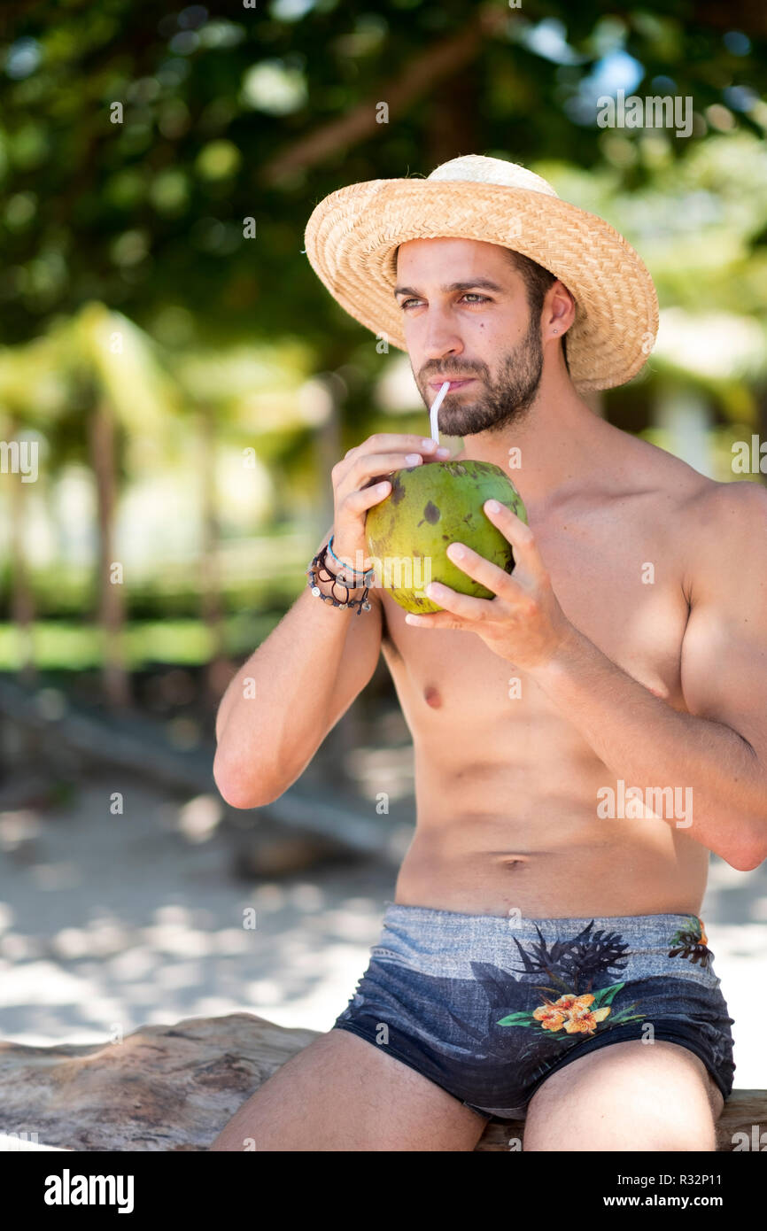 A handsome young man with no shirt on a tropical beach - Stock Image