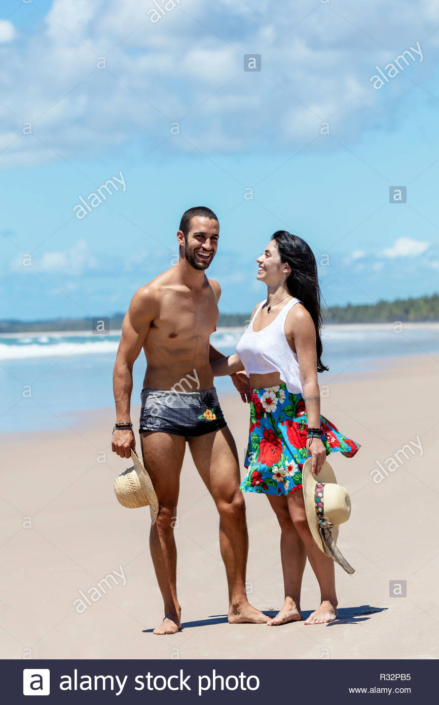 An attractive young couple in love on an idyllic beach in the tropics - Stock Image