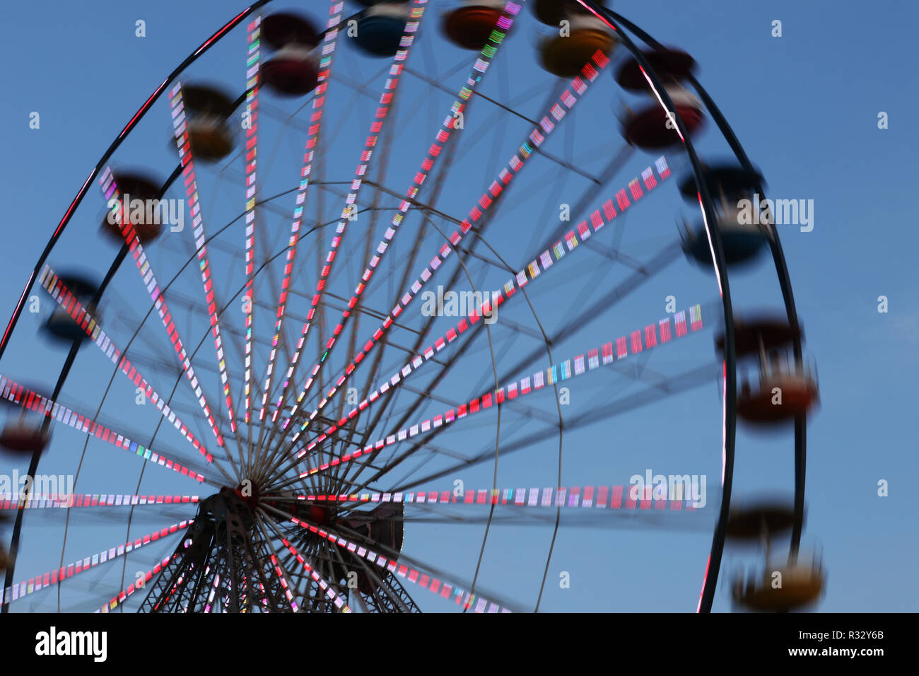 Ferris Wheel carnival ride against blue sky at dusk. Motion blur. Canfield Fair. Mahoning County Fair. Canfield, Youngstown, Ohio, USA. - Stock Image