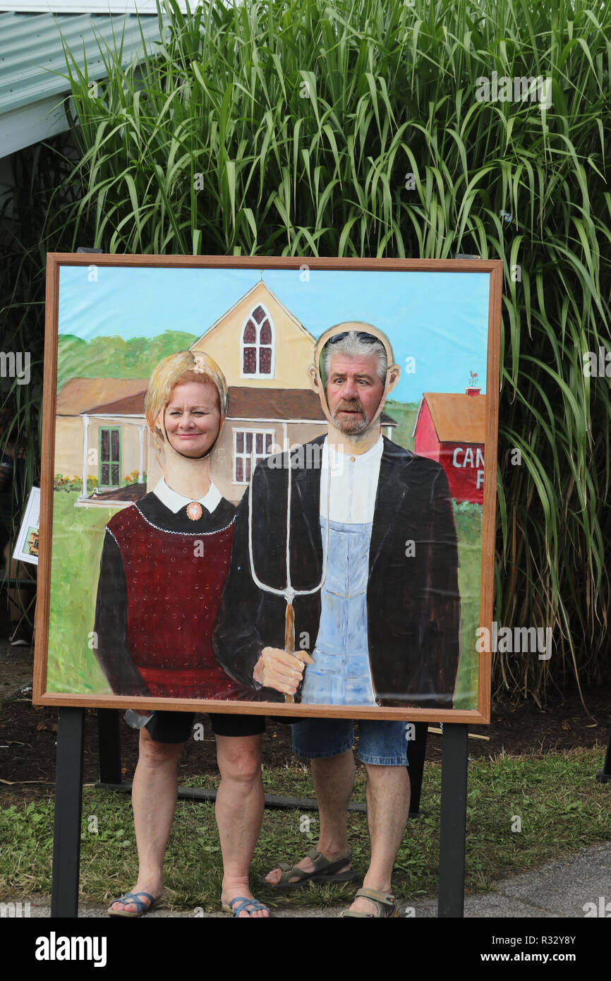 Fun painting of American Gothic, originally by Grant Wood, with face cutouts so people can show their faces. Canfield Fair. Mahoning County Fair. Can - Stock Image