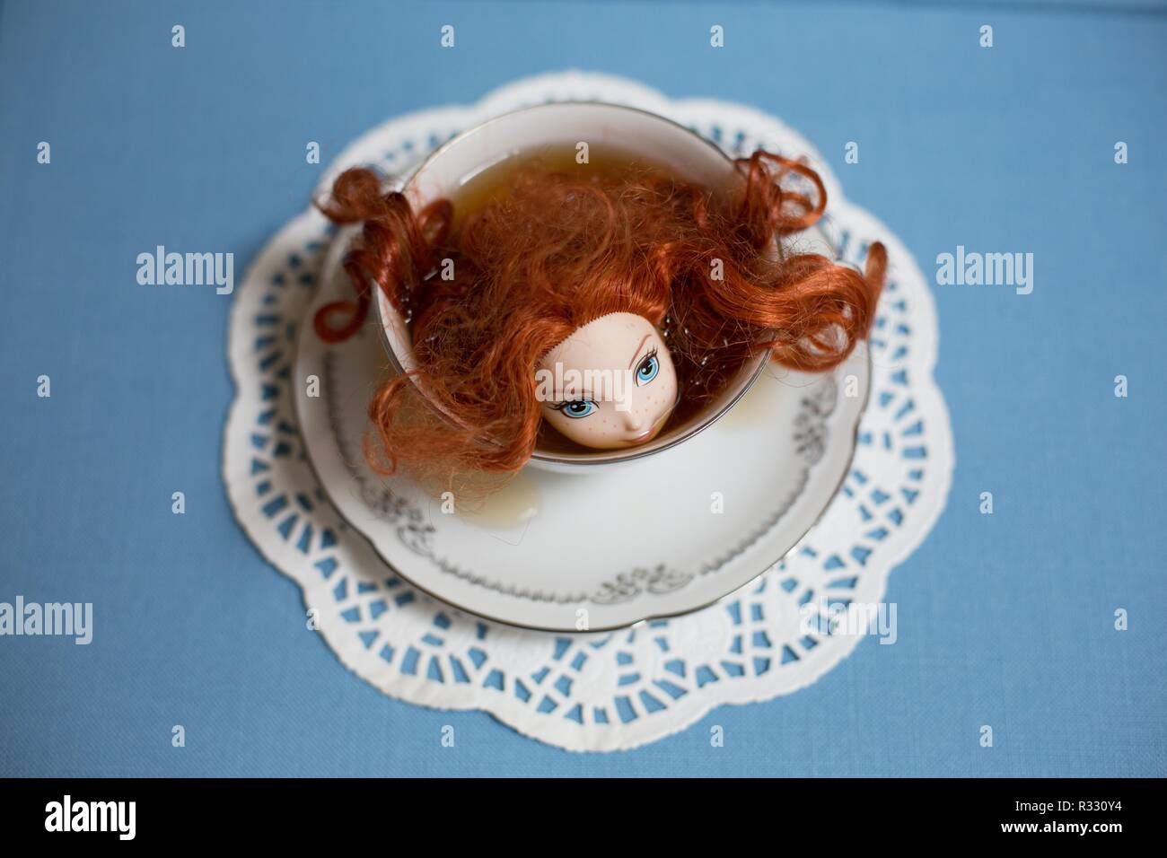 Surreal image of red-headed doll in a cup of tea. - Stock Image