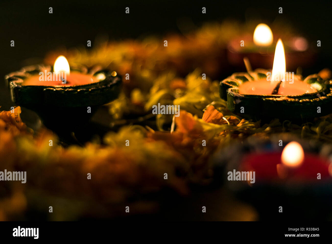 Lit diyas placed on flowers for celebrating diwali and dhanteras in Asia Stock Photo