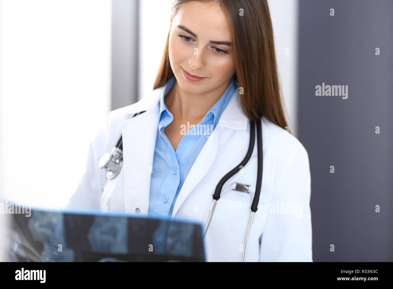 Doctor woman examining x-ray picture while standing near window in hospital. Surgeon or orthopedist at work. Medicine and healthcare concept - Stock Image