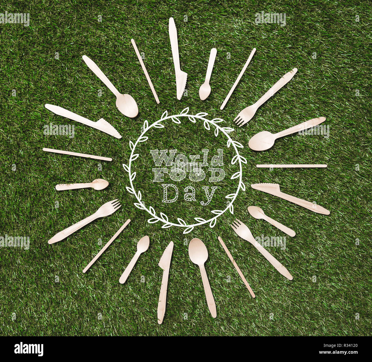 top view of wooden spoons with forks and knives in shape of sun lying on grass, world food day inscription - Stock Image