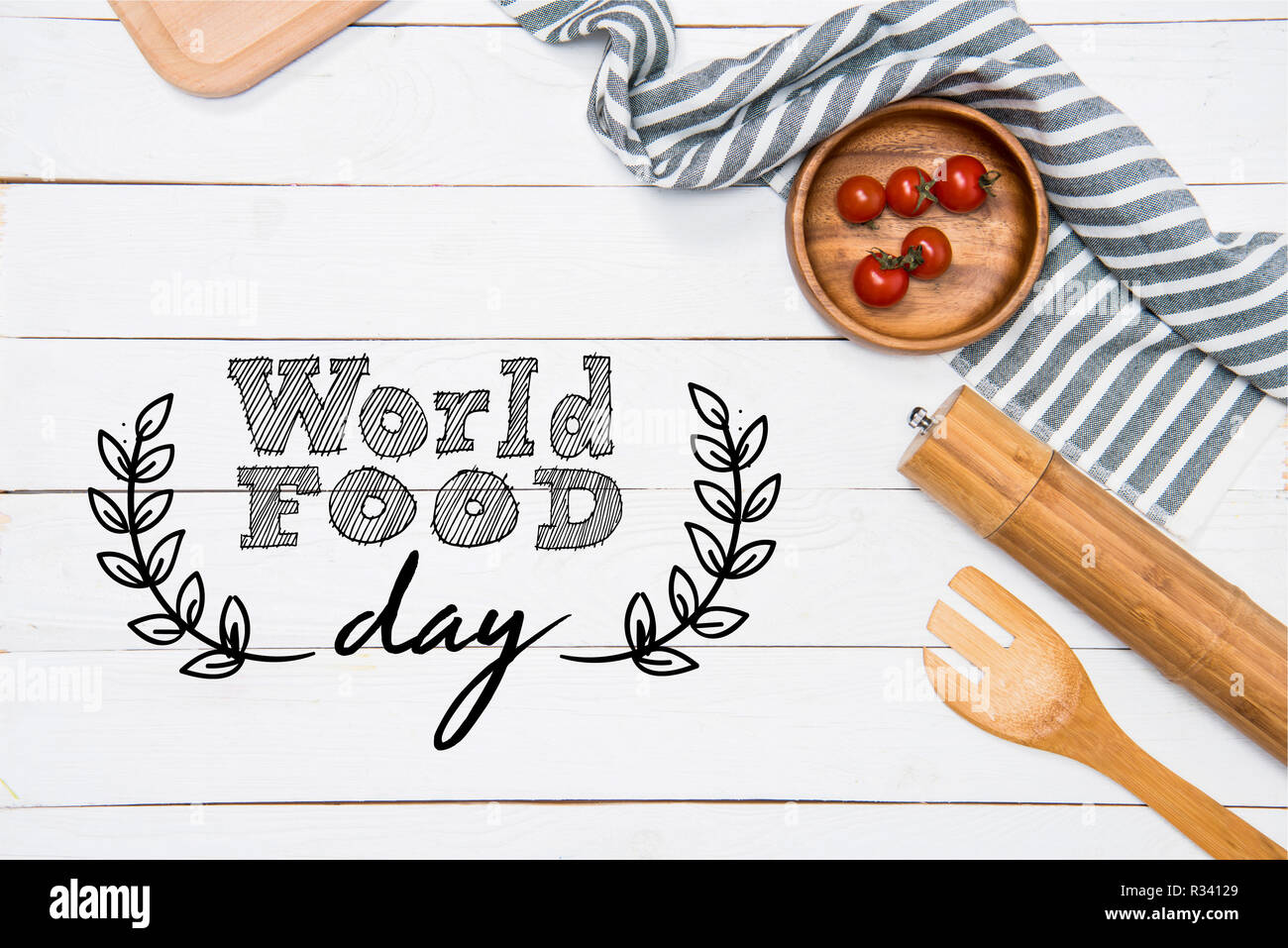Cherry tomatoes with wooden spatula and salt grinder with table cloth on tabletop, world food day inscription - Stock Image