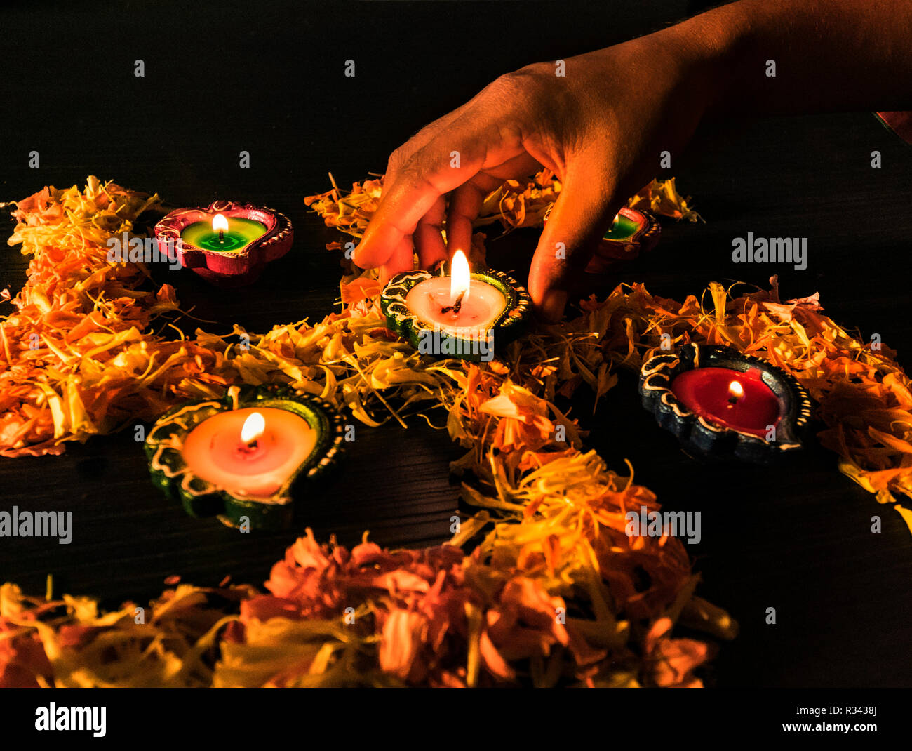 A girl lighting diyas for celebrating diwali and dhanteras festival in India Stock Photo