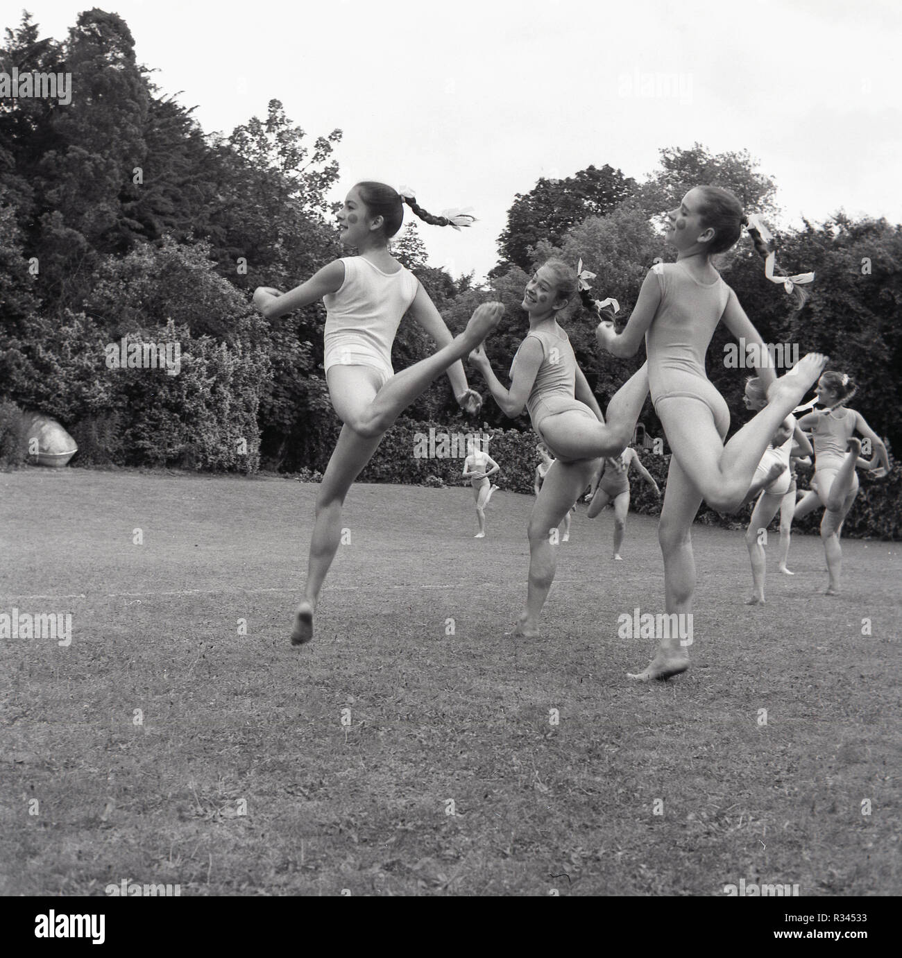 1967, tring arts festival, young female ballet dancers from the Arts Educational School performing together outside in a grass field. Founded as the sister school of the London school, it is now know as the Tring Park School fo the Performing Arts, a specialist English boarding school for gifted young people in dance, music and theatre. - Stock Image