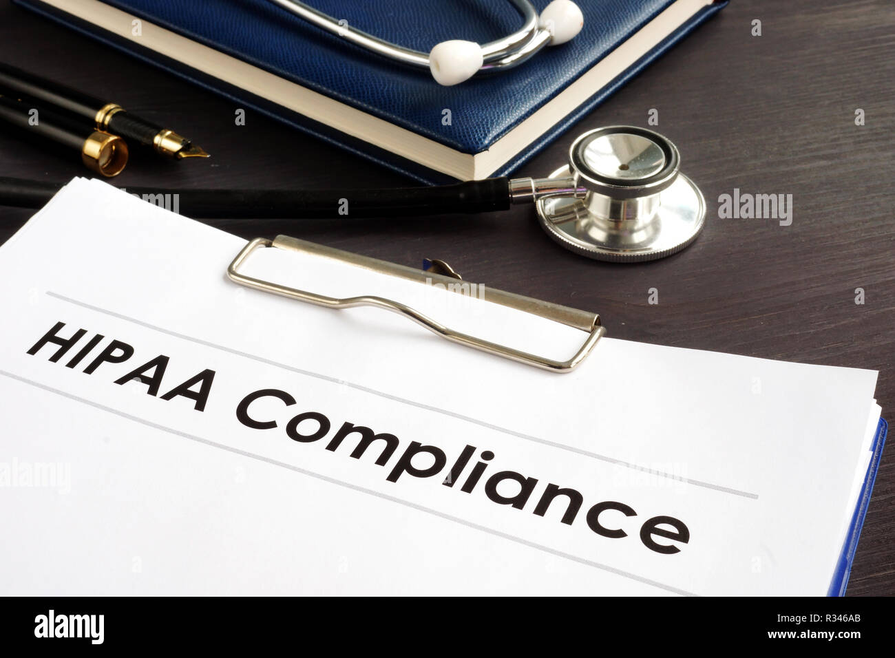 HIPAA Compliance documents with clipboard on a desk. - Stock Image