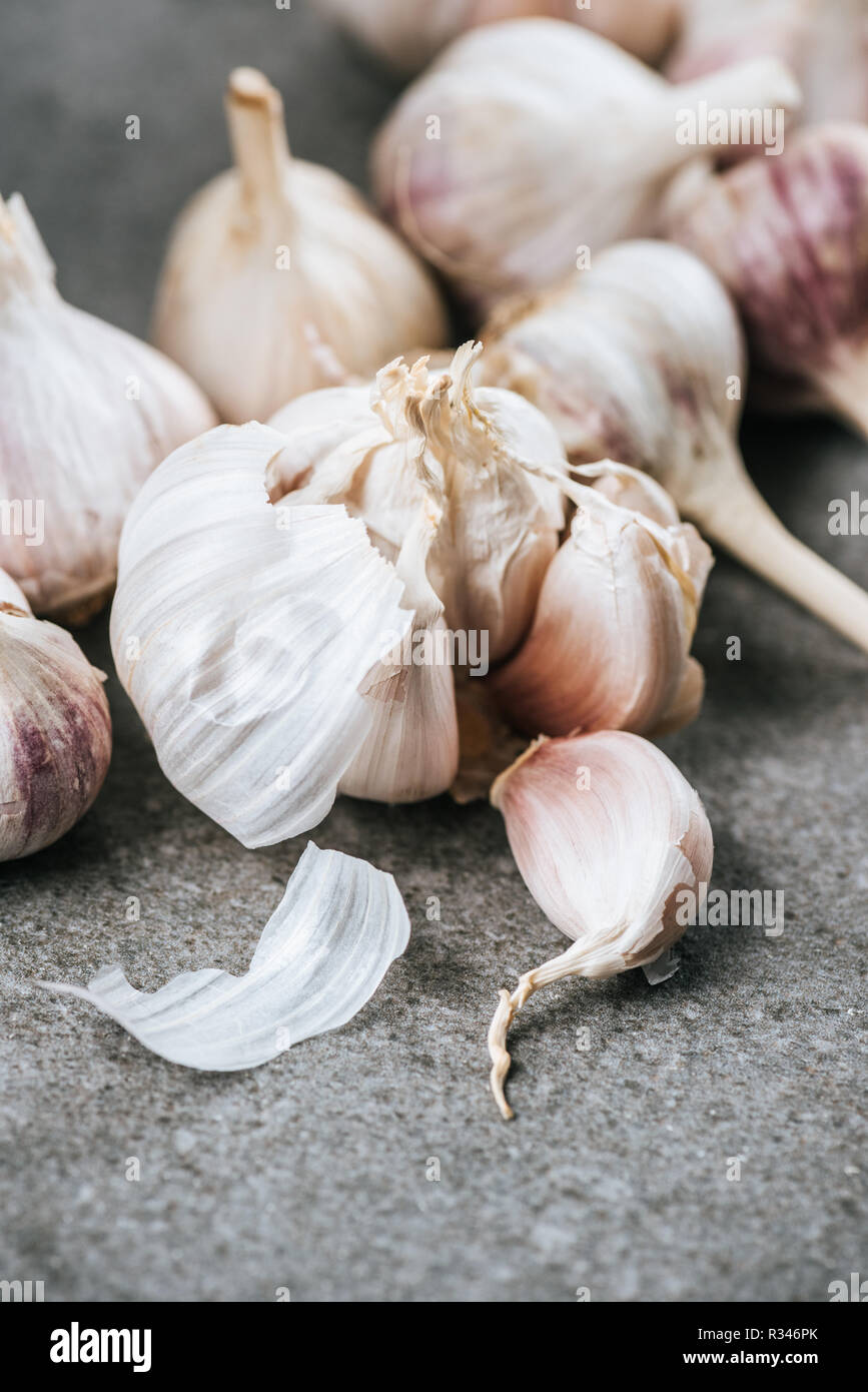 garlic bulbs and peeled cloves on grey textured surface - Stock Image